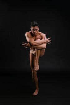 Młody tancerz obejmując kolano