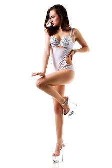Młody taniec szczupła piękna brunetka kobieta w sexy biały kostium i buty na obcasie na białym tle nad białym tle