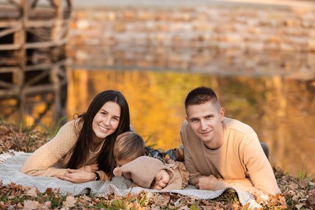 Młody tata i mama z córeczką i synkiem bawią się na kocu w pobliżu stawu w jesiennym parku