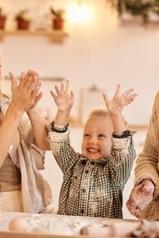 Młody tata, mama i ich synek dobrze się bawią, bawiąc się i gotując w kuchni