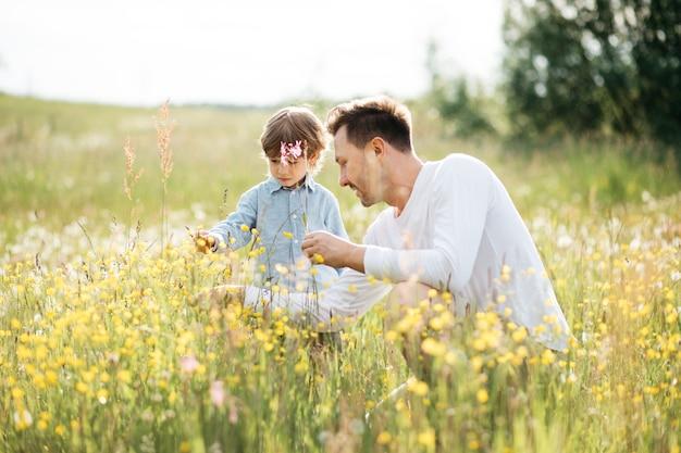 Młody tata spędza czas ze swoim synkiem na łonie natury, zbierając bukiet dla mamy z polnych kwiatów, dzień ojca