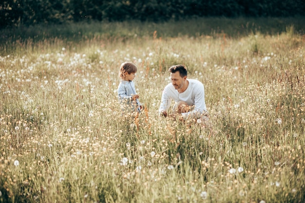 Młody Tata Spędza Czas Ze Swoim Synkiem Na łonie Natury, Zbierając Bukiet Dla Mamy Z Polnych Kwiatów Premium Zdjęcia