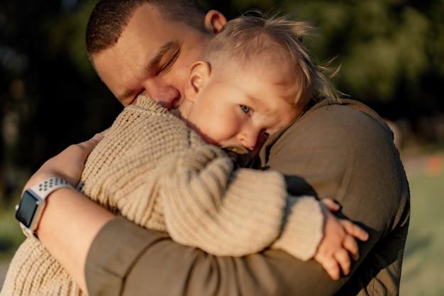Młody tata z zamkniętymi oczami przytula małego synka kładąc głowę na jego ramieniu i ssąc smoczek. stoją w parku. zdjęcie wysokiej jakości