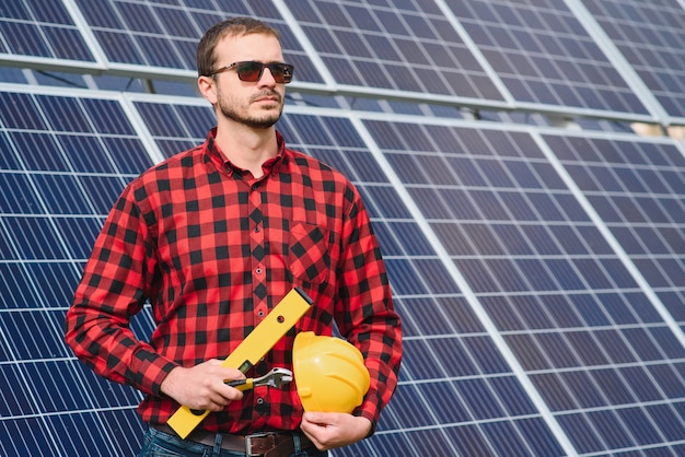 Młody technik instalujący panele słoneczne na dachu fabryki