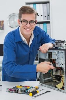 Młody technik pracuje na łamanym komputerze