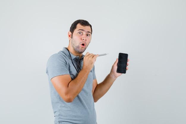 Młody technik próbuje otworzyć swój smartfon za pomocą wiertarki w szarym mundurze i wygląda na zaskoczonego, widok z przodu.