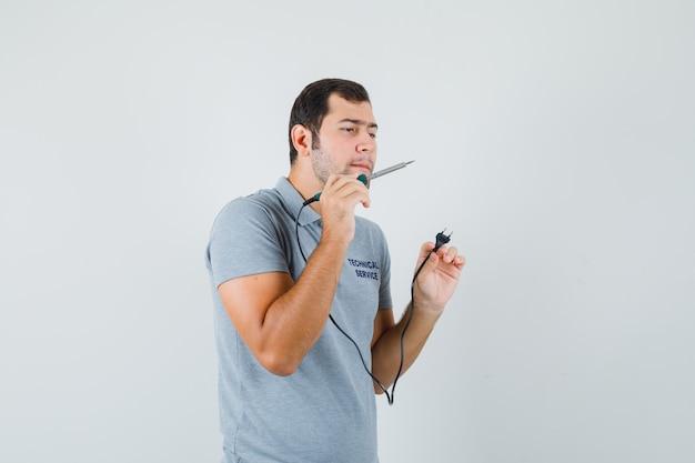 Młody technik trzymający w dłoni śrubokręt i usiłujący otworzyć tył telefonu w szarym mundurze i wyglądający na skupionego.