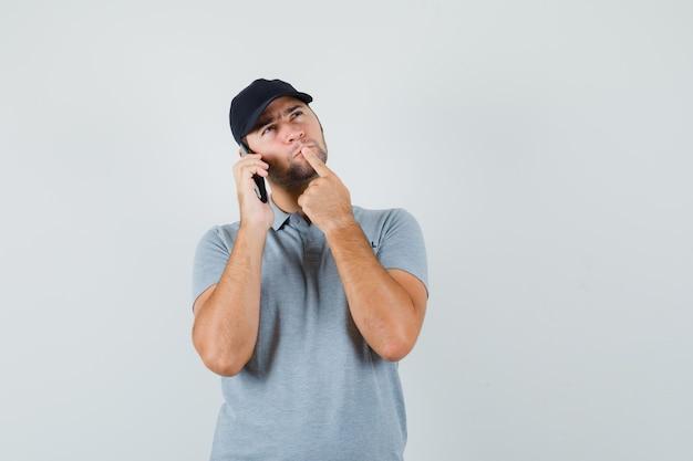 Młody technik w szarym mundurze stoi w myślącej pozie podczas rozmowy przez telefon i zamyślenia.