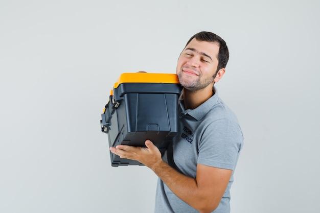 Młody technik w szarym mundurze trzyma skrzynkę z narzędziami obiema rękami, uśmiechnięty i optymistycznie wyglądający.