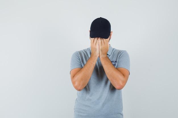 Młody technik w szarym mundurze zakrywającym twarz rękami i wyglądający na przygnębionego.