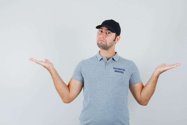 Młody technik wykonujący gest wagi w szarym mundurze i wyglądający na zdezorientowanego.