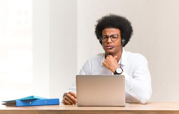 Młody telemarketer czarny mężczyzna kaszle, chory z powodu wirusa lub infekcji