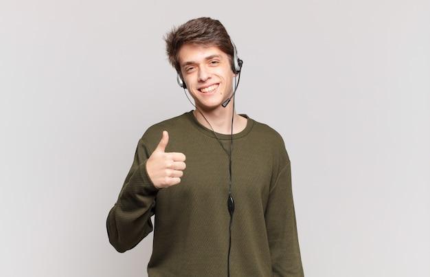Młody telemarketer czuje się dumny, beztroski, pewny siebie i szczęśliwy, uśmiecha się pozytywnie z kciukami w górę