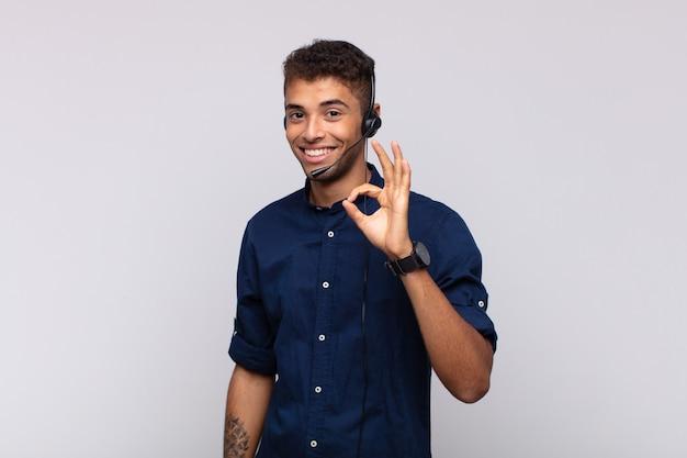 Młody telemarketer czuje się szczęśliwy, zrelaksowany i usatysfakcjonowany, okazuje aprobatę z dobrym gestem, uśmiecha się