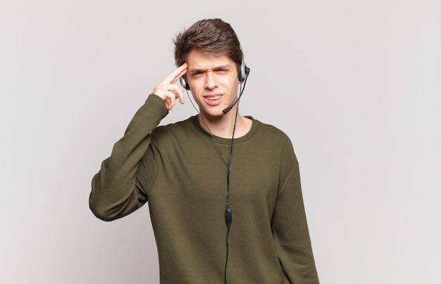 Młody telemarketer czuje się zdezorientowany i zdezorientowany, pokazując, że jesteś szalony, szalony lub oszalały