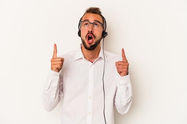 Młody telemarketer kaukaski mężczyzna z tatuażami na białym tle wskazujący do góry z otwartymi ustami.