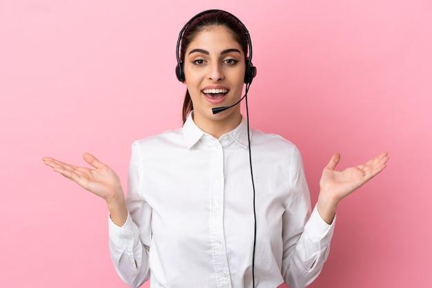 Młody telemarketer na białym tle ze zszokowanym wyrazem twarzy
