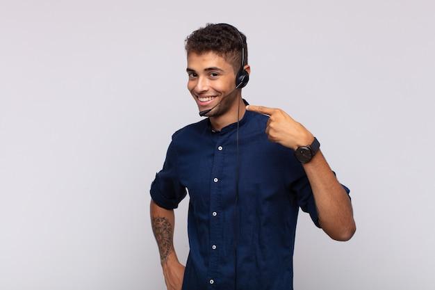 Młody telemarketer uśmiecha się pewnie, wskazując na swój szeroki uśmiech, pozytywne, zrelaksowane, zadowolone nastawienie