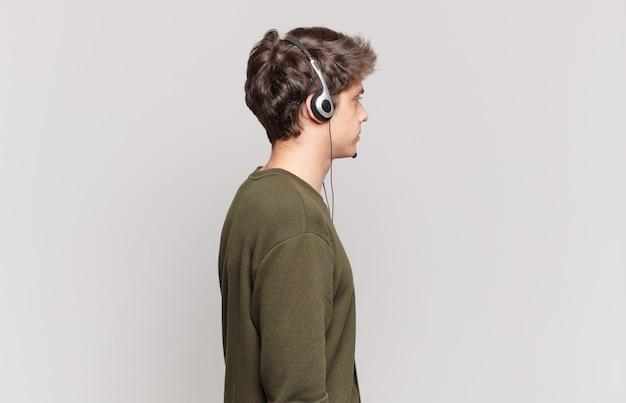 Młody telemarketer w widoku profilu, który chce skopiować przestrzeń do przodu, myśląc, wyobrażając sobie lub marząc na jawie