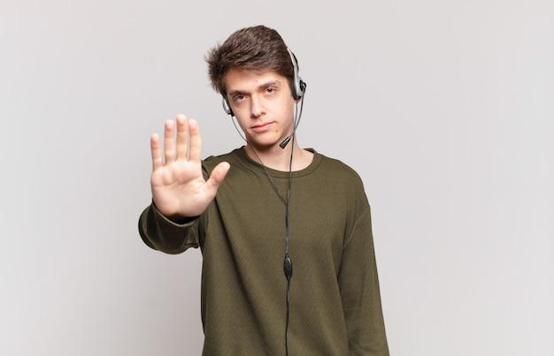 Młody telemarketer wygląda poważnie, surowo, niezadowolony i zły pokazując otwartą dłoń, wykonując gest zatrzymania
