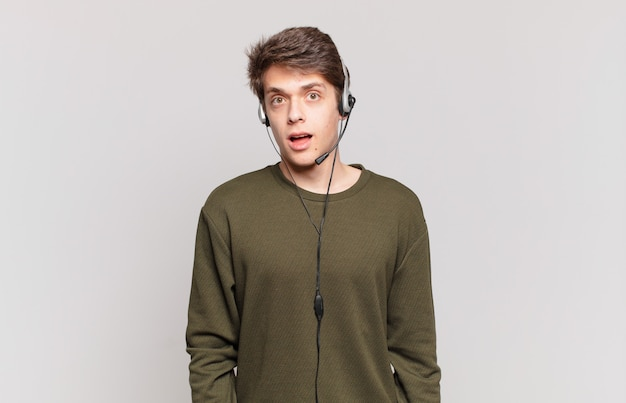 """Młody telemarketer wyglądający na bardzo zszokowanego lub zaskoczonego, patrzący z otwartymi ustami i mówiący """"wow"""