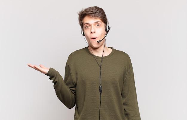 Młody telemarketer wyglądający na zaskoczonego i zszokowanego, z opuszczoną szczęką, trzymający przedmiot z otwartą dłonią z boku