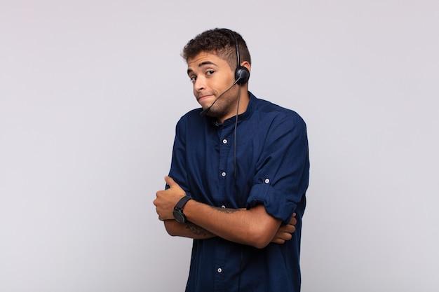 Młody telemarketer wzrusza ramionami, czuje się zdezorientowany i niepewny, wątpi z założonymi rękami i zdziwionym spojrzeniem