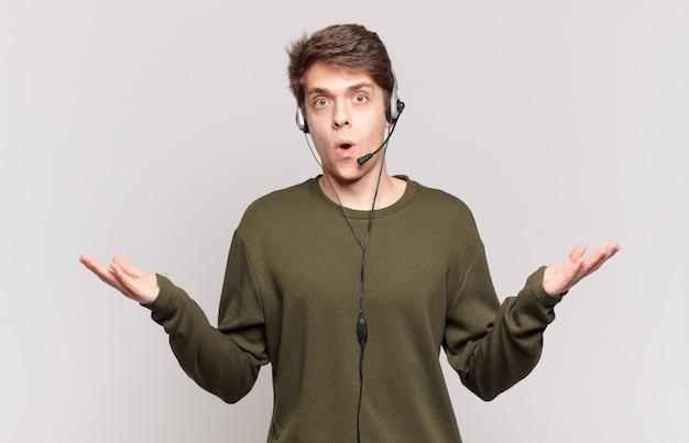 Młody telemarketer z otwartymi ustami i zdumiony, zszokowany i zdumiony niewiarygodną niespodzianką
