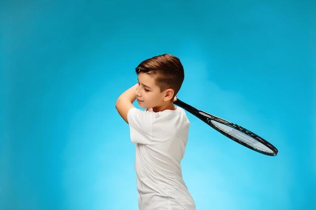 Młody tenisista na niebieskiej przestrzeni.