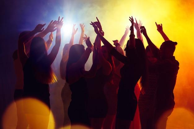 Młody. tłum ludzi w sylwetce podnosi ręce na parkiecie na neonowym tle. życie nocne, klub, muzyka, taniec, ruch, młodzież. żółto-niebieskie kolory i poruszające dziewczyny i chłopcy.