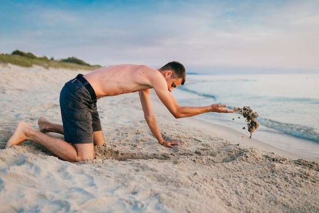 Młody topless boso mężczyzna w krótkich spodenkach, stojąc na kolanach i kopiąc dół rękami na plaży za morzem w letni wieczór.