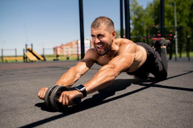 Młody topless muskularny sportowiec z trymerem brzucha, stojący na kolanach, tarzając się do przodu po boisku
