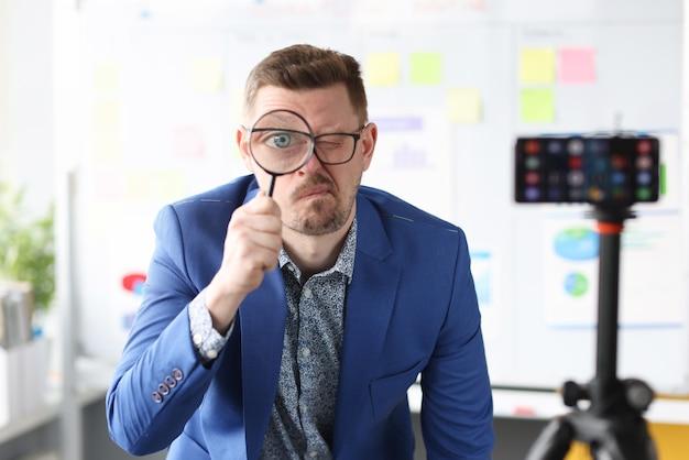 Młody trener biznesu trzymając szkło powiększające w pobliżu oka przed aparatem telefonu komórkowego
