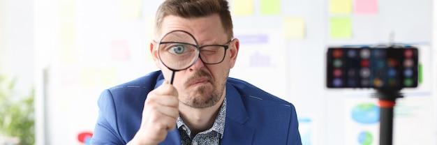 Młody trener biznesu trzymający szkło powiększające w pobliżu oka przed aparatem telefonu komórkowego mobile