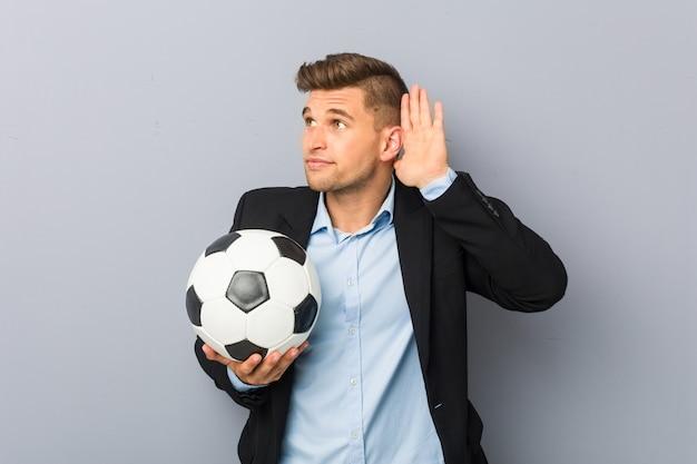 Młody trener piłki nożnej próbuje słuchać plotek.