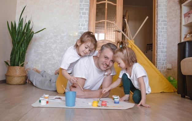 Młody troskliwy ojciec uczy się malować ze swoimi córkami, mężczyzna leży na podłodze i uczy dziewczynki rysować kwiaty, meble domowe.