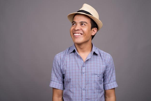 Młody turysta azjatycki mężczyzna w kapeluszu gotowy na wakacje przed szarej ścianie