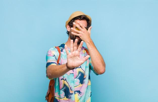 Młody turysta brodaty mężczyzna zakrywający twarz ręką
