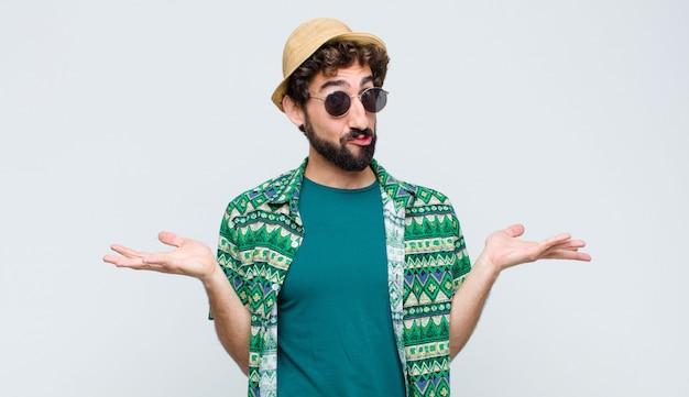 Młody turysta czuje się zdziwiony i zdezorientowany, wątpiąc, ważąc lub wybierając różne opcje z zabawnym wyrazem twarzy na białej ścianie