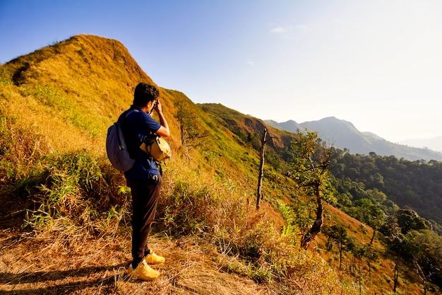 Młody turysta fotografuje wzdłuż ścieżki trekkingu. fotograf bierze fotografię przy halnym szczytem.