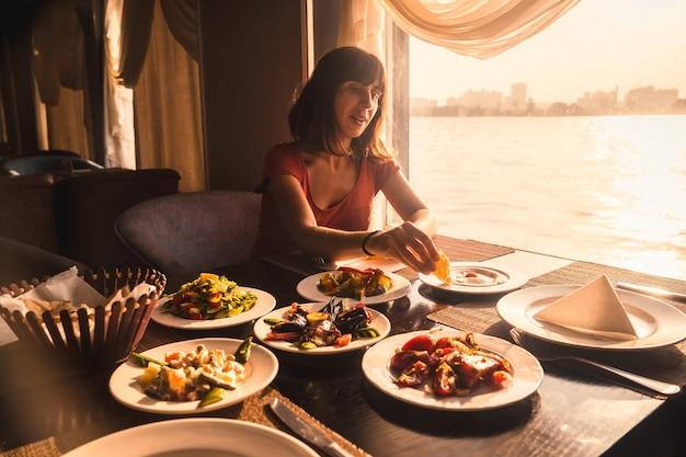 Młody turysta jedzący obiad na łódce na nilu