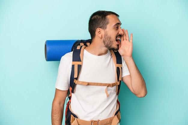 Młody turysta kaukaski mężczyzna na białym tle na niebieskim tle krzycząc i trzymając dłoń w pobliżu otwarte usta.