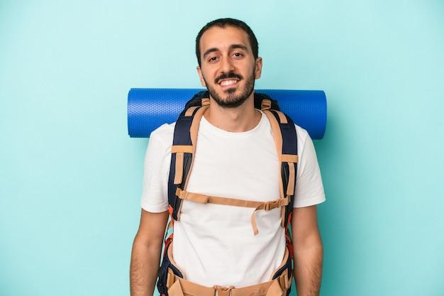Młody turysta kaukaski mężczyzna na białym tle na niebieskim tle szczęśliwy, uśmiechnięty i wesoły.