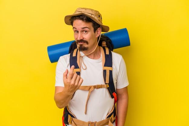 Młody turysta kaukaski mężczyzna na białym tle na żółtym tle wskazując palcem na ciebie, jakby zapraszając zbliżyć się.