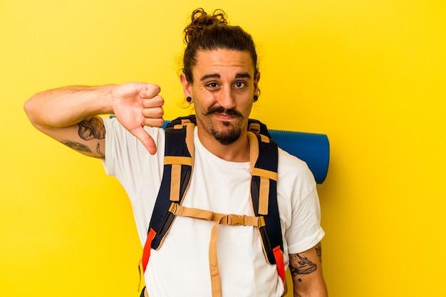 Młody turysta kaukaski mężczyzna z długimi włosami na białym tle na żółtym tle pokazując gest niechęci, kciuk w dół. koncepcja niezgody.