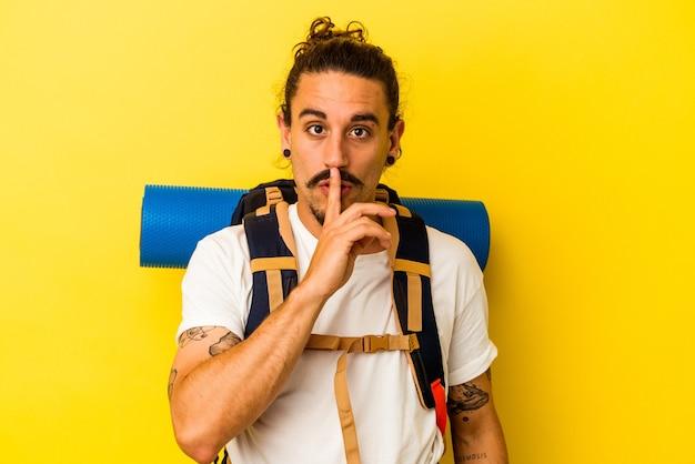 Młody turysta kaukaski mężczyzna z długimi włosami na białym tle na żółtym tle zachowując tajemnicę lub prosząc o ciszę.