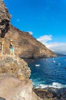 Młody turysta latem z punktu widzenia spoglądający i cieszący się zatoką puerto de puntagorda, wyspa la palma, wyspy kanaryjskie. hiszpania