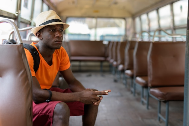 Młody turysta mężczyzna myśli trzymając telefon komórkowy i jeżdżąc autobusem w bangkoku w tajlandii