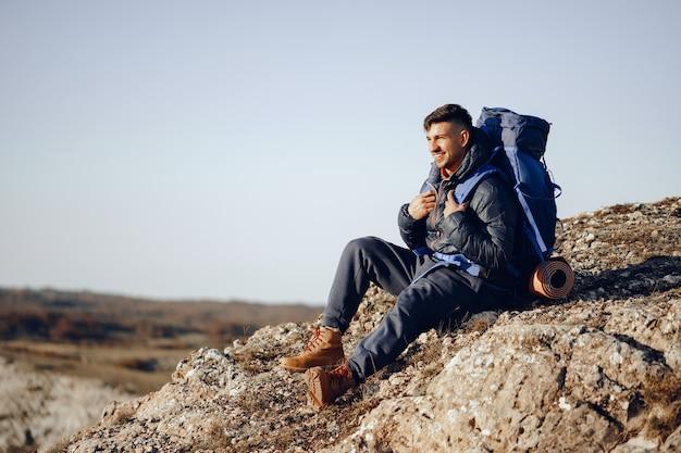Młody turysta mężczyzna siedzi i odpoczywa na postoju