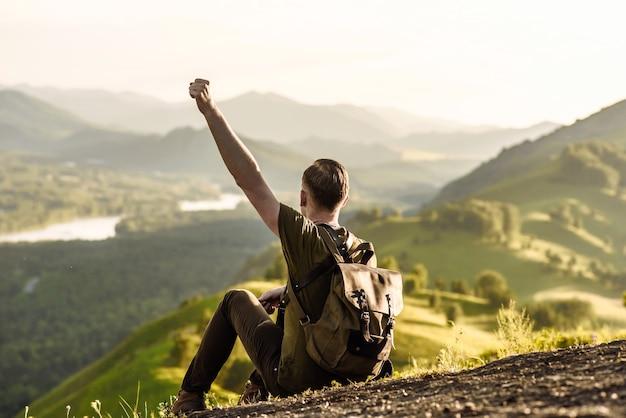 Młody turysta mężczyzna siedzi z plecakiem i patrzy na góry i rzekę z podniesioną ręką
